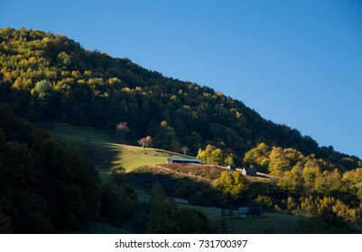 Little village in the mountains in the golden morning light - near the autumn forest