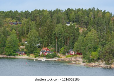 Little villages on the one of the Swedish archipelagos. Houses surrounded with beautiful green nature, water and sky. Traditional Swedish archipelago island and typical red houses