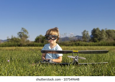 The little villain kid and his new RC plane, outdoors on grass