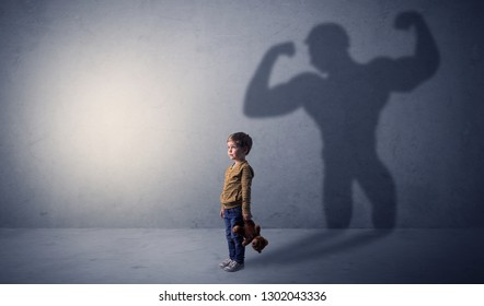 Little waggish boy in an empty room with musclemen shadow behind