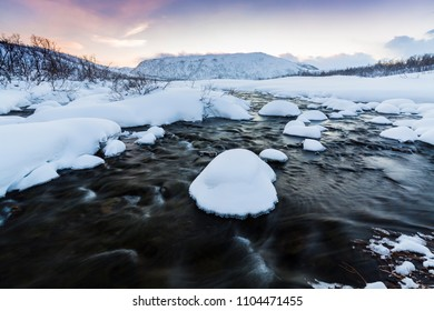 A little water stream with rocks on the foreground with a arctic, snowy winter landscape at the background. The sky is clear, multiple and vibrant colors are are visible during sunset.