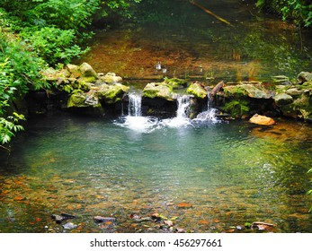 The little waterfall in the brook with the clear water in summer