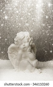 Little white angel on a silver  background.