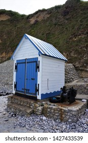 Little white and blue painted wooden fishing cabin on the beach in Grandes Dalles Normandy France