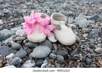Little white boots with pink flowers on a stoned beach