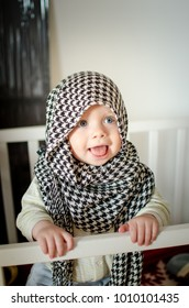 A little white boy in keffiyeh scarf stands in his white bed and smiles.