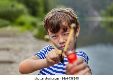 Little white boy is standing in forest or pakr with slingshot in his hands and preparing for shooting strewing up his eyes, boy is aiming.