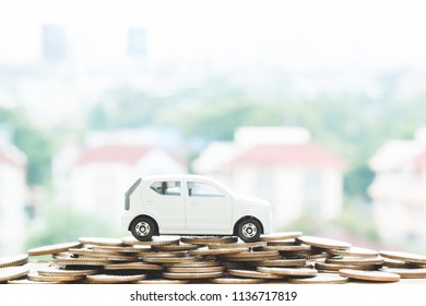 Little white car over a lot of money stacked coins with background house. for loans costs concept. with filter Tones retro vintage effect ,Warm tones.