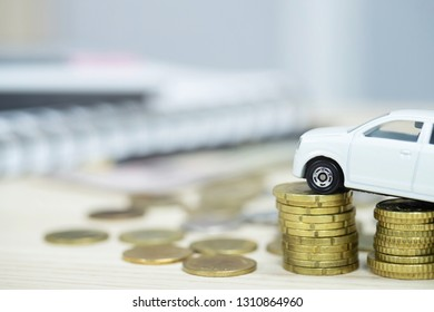 Little white car over a lot of money stacked coins and background accounting document calculate installment. for bank loans costs. insurance, car finance concept. buy and pay by down payment a car.