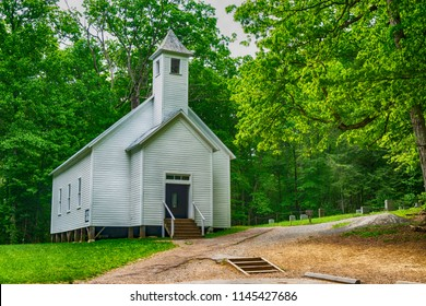 Little White church in Cades Cove surrounded with greenery.