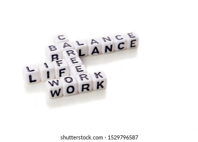 little white dices with black letters forming a crossword with the theme work life balance as equilibrium of professional and personal family life on white background