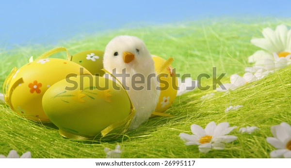 Little white Easter chick and Painted Colorful Easter Egg on green Grass