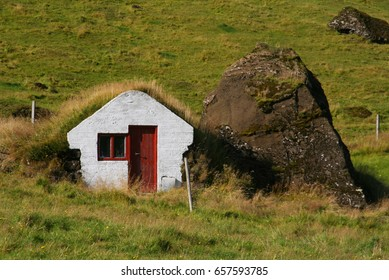 Little white elf house with turf roof and a mossy stone in Iceland