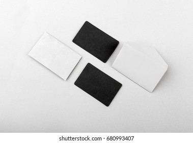 Little white envelopes and business cards black on white background