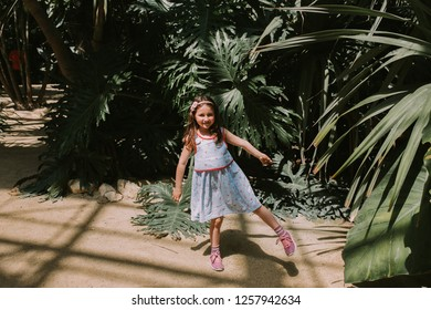 Little white girl in a blue dress is standing on one leg in a Botanical garden Terra Botanica in Angers, France