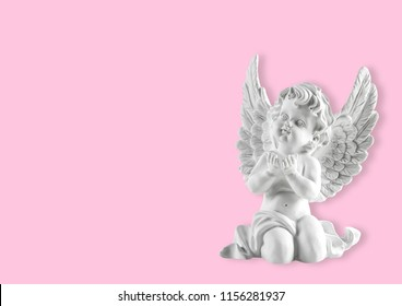 Little white guardian angel on pink background