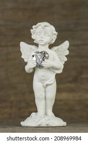 little white guardian angel on wooden background