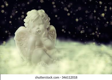 Little white guardian angel on dark background.