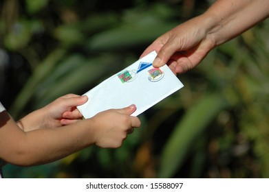 A little white hand of a caucasian girl toddler receiving a letter from her grandmother in the garden during sunset