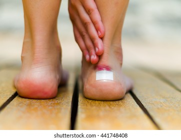 Little white patch on the ankle of feet, skin red that hurts. Wooden floor