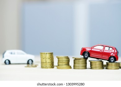 Little white and red two car over a lot of money stacked coins. for  bank loans costs finance. insurance, buying car finance concept. buy and pay by installments down payment a car.