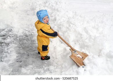 Little White Toddler with a huge shovel as a snowblower clearing snow from the road. Strong cyclone caused heavy rainfall and snow.