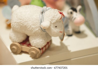 A little white toy sheep with cute wheels with some other tiny toys at the background.