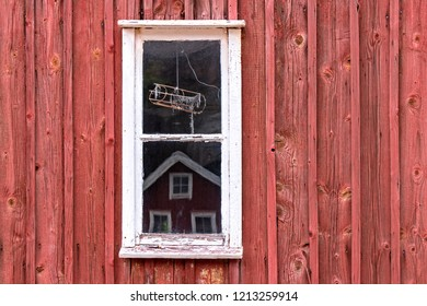 A little window in front of a typival scandinavian building with falu red. Was seen in Sweden.