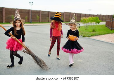 Little witch with broom and her friends walking down road on halloween evening