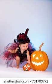 Little witch girl child laughing among pumpkins and candles on a white background.
