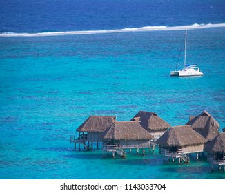Little wooden bungalows of a luxury hotel resort in breathtaking turquoise sea on a windy summer day. Strong winds blowing past a white sailboat and oceanfront overwater villas. Holiday accommodation.