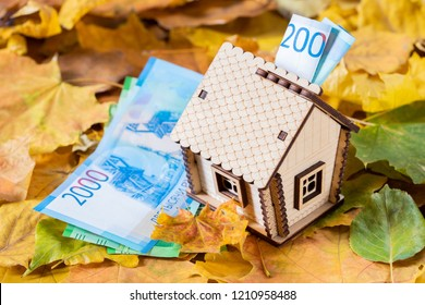 Little Wooden House Moneybox With Russian Money Banknotes Of 2000 Rubles Wrapped On Autumn Leaves With Russian Banknotes Of Two Thousands Rubles Close Up.