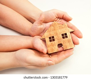 A little wooden house in women's and child's hand. real estate, charity, family and home idea