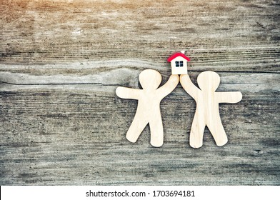 little wooden men and house with blank space for text or logo. Symbol of construction, family, sweet home concept