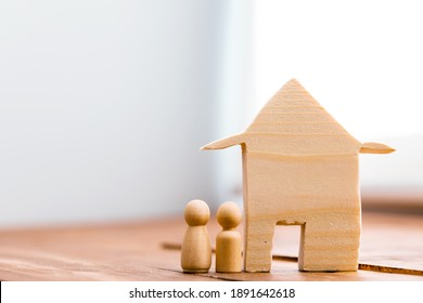 Little wooden men and house miniature close up
