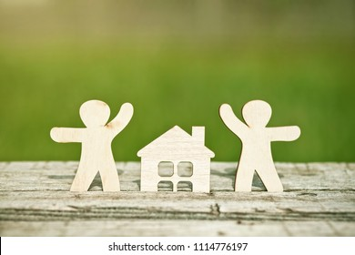 little wooden men and house on natural background. Symbol of construction, family, sweet home concept