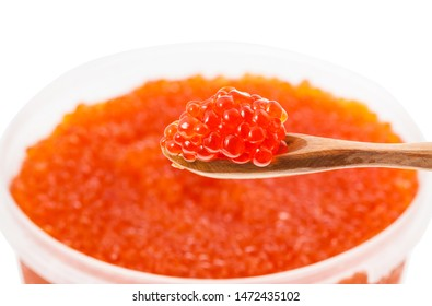 little wooden spoon with salted russian red caviar of sockeye salmon fish with blurred plastic container with red roe of pink salmon on background isolated on white