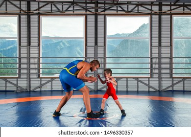 A little wrestler boy in a sports tights wrestles with an adult male wrestler on a wrestling carpet in the gym. The concept of child power and martial arts training. Teaching Greco-Roman wrestling