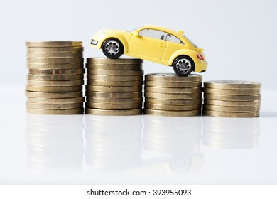 Little yellow car over a lot of stacked coins