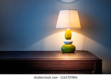 Little yellow, gray and green lamp on a wooden dresser or a night table, illuminating the wall covered with wallpaper at night or late evening. Soft and warm interior mood.