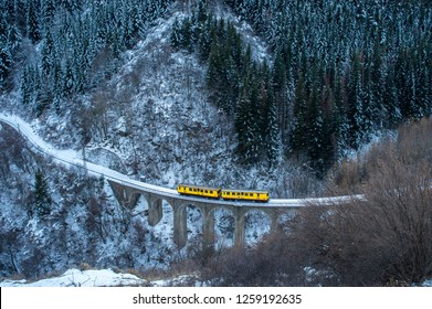 Little Yellow Train travelling in winter, in Mont-Louis, Pyrenees-Orientales, France
