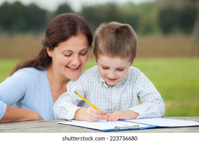 Little young boy in white shirt and his happy mother having fun writing or drawing with a pencil on a sheet of paper on wood table in the park