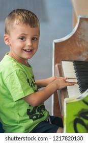 Little young caucasian boy playing on the piano outside train station