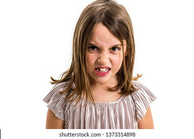 Little young girl is angry, mad, disobedient with bad behaviour. Children making the act of insubordination and disobedience, yelling, showing teeth, behaving crazy after permissive parenting.