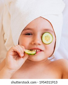 Little young girl on spa, with cucumber on the face