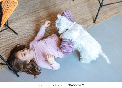 Little young girl playing with dog on the floor at home