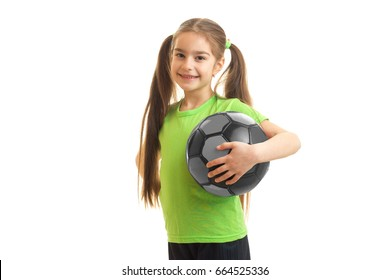 little young girl with soccer ball in hand smiling on camera isolated on white background