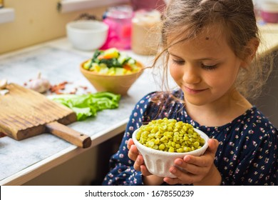 Little young vegan, vegetarian girl kid with food in hands. Healthy eating. Family  health care concept. Green peas cooked