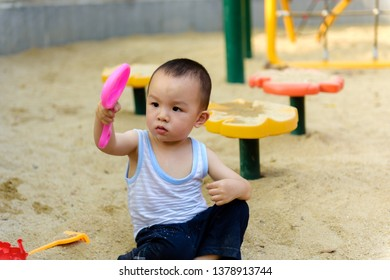 LittleAsian baby boy playing in  sandpit with toys outside in park