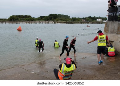 Littlehampton, West Sussex, UK, June 15 2019, River Arun swim over the classic Ironman distance of 3.8km from Ford to Littlehampton. Helping hand at the finish.
